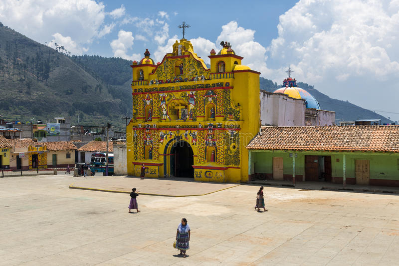 The colorful church of San Andres Xecul and three local Mayan woman walking on the street in Guatemala royalty free stock image