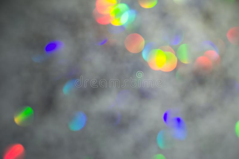 Colorful circles of light abstract background. Holiday texture. Glitter multicolored light spots on gray backdrop stock image