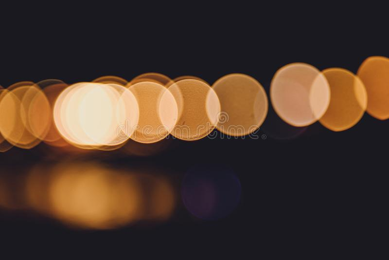 Colorful city lights with bokeh effect reflected over sea background at dusk stock photography