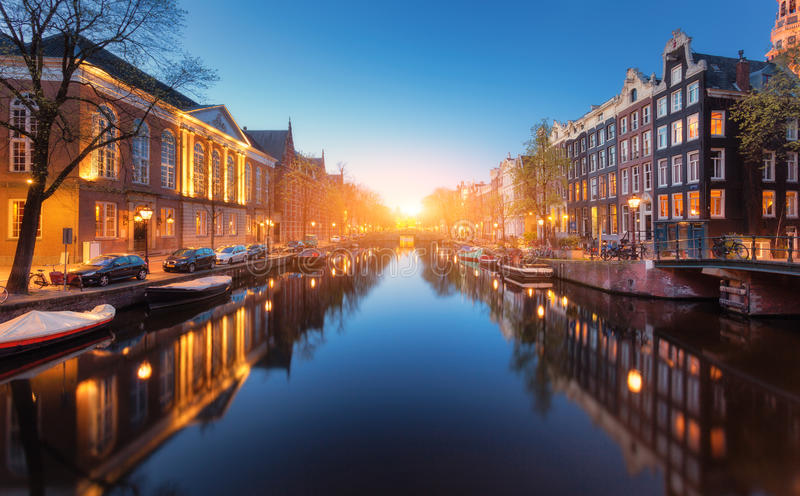 Colorful cityscape at sunset in Amsterdam, Netherlands. Reflected city lights in water with blue sky at twilight. Night illumination of buildings and boats on stock images