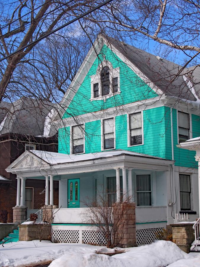 Colorful clapboard house with large porch. In winter stock photo