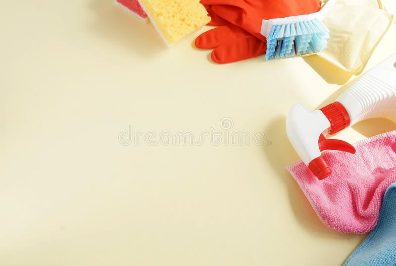 Colorful cleaning set for different surfaces in kitchen, bathroom and other rooms. Empty place for text or logo on pale yellow background. Cleaning service stock photography