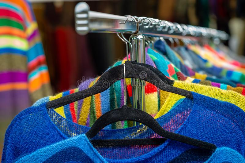 Colorful clothes hang on shelf in a market royalty free stock images