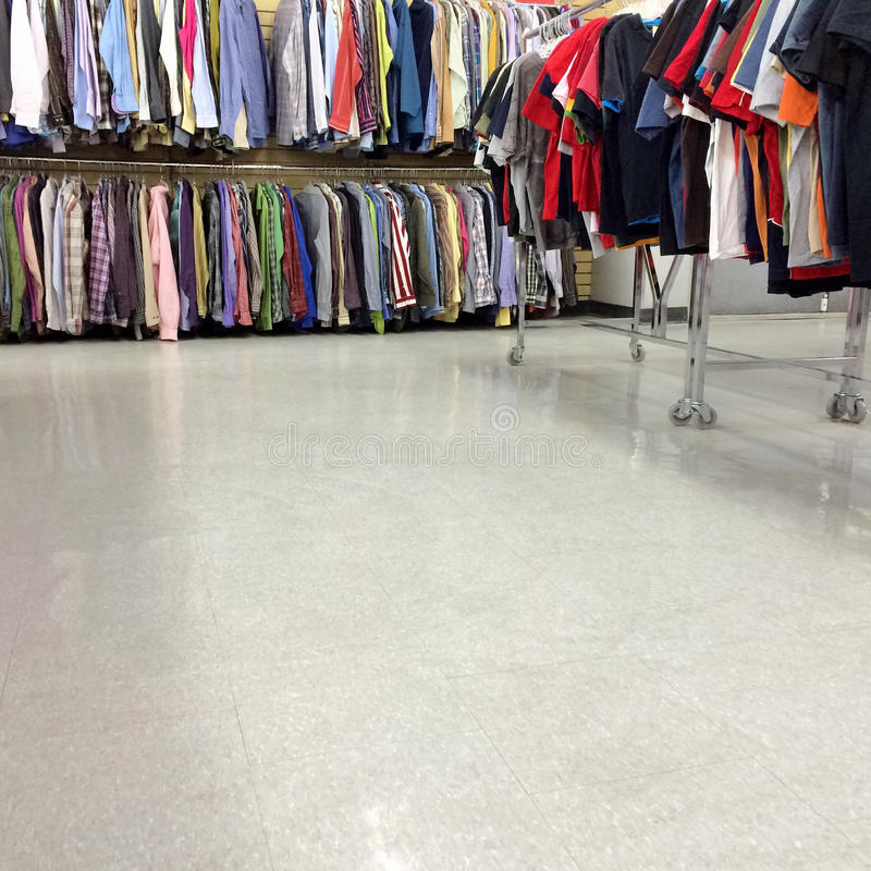Colorful clothes for sale in a second hand store. With empty floor as copy space royalty free stock photo