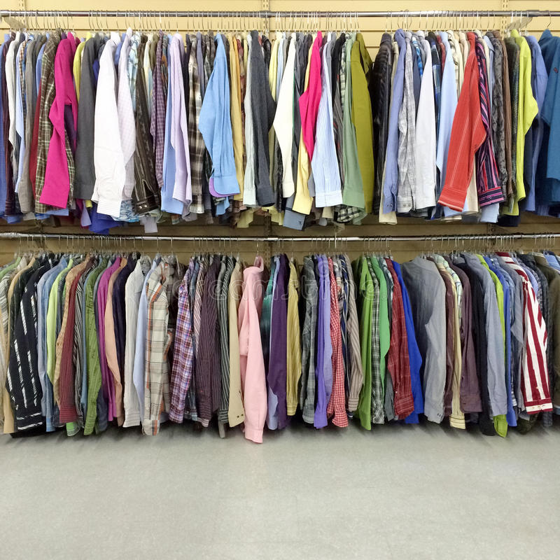 Colorful clothes in a second hand store. Colorful clothes for sale in a second hand store royalty free stock photography