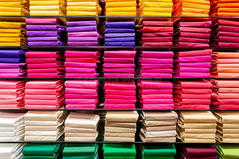 Colorful clothing neatly on shelves stock photos