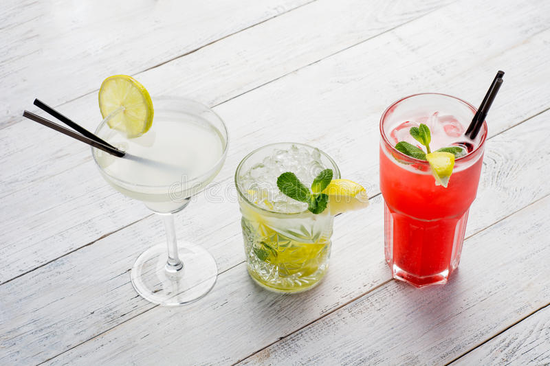 Colorful cocktails set. Mojito , Margarita, red alcohol cocktail on wooden table close up. royalty free stock photos