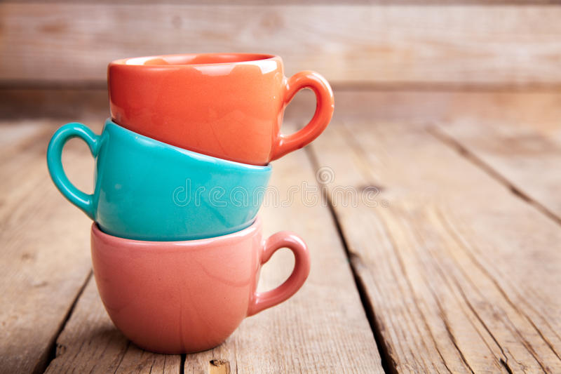 Colorful coffee cups on wooden table over grunge background royalty free stock photos
