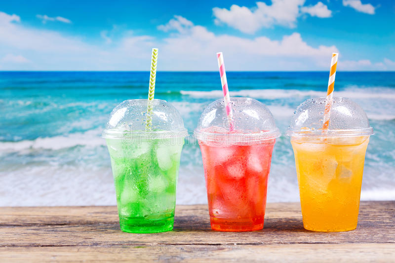 Colorful cold drinks in plastic cups on the beach stock photos