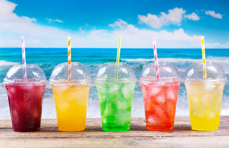 Colorful cold drinks in plastic cups on the beach royalty free stock images