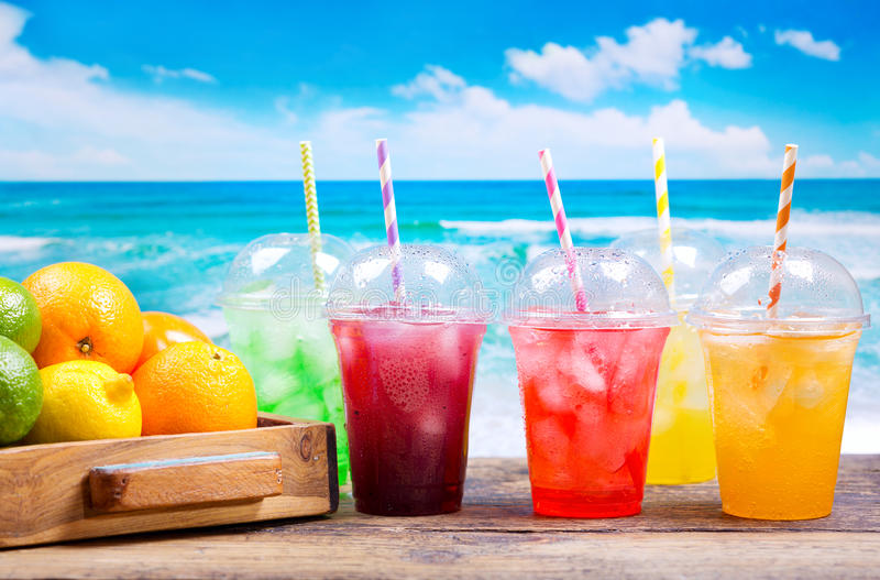 Colorful cold drinks in plastic cups on the beach. Colorful cold drinks in plastic cups with ice and fresh fruits on the beach royalty free stock photography