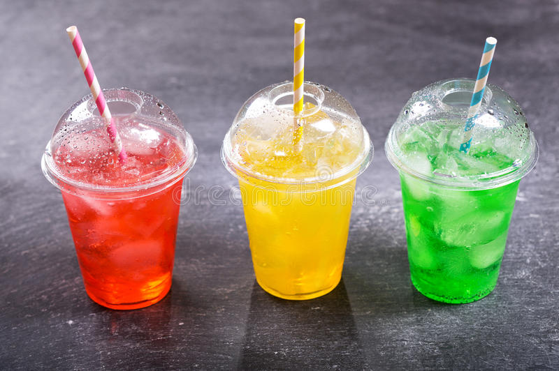 Colorful cold drinks in plastic cups stock photos
