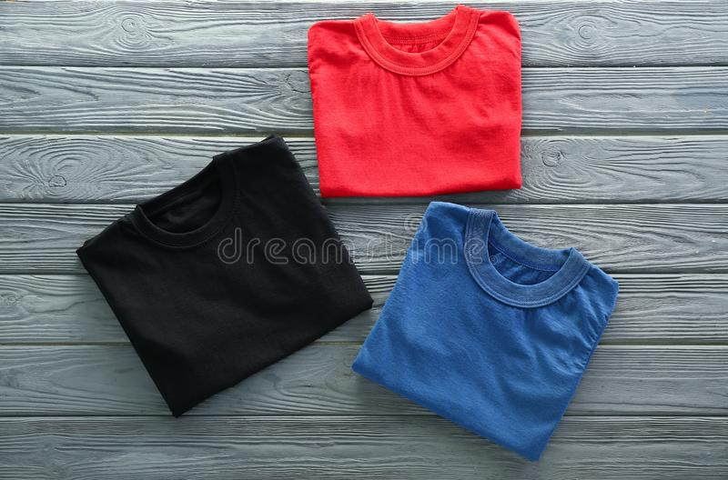 Colorful collection of t-shirts on wooden background stock photo
