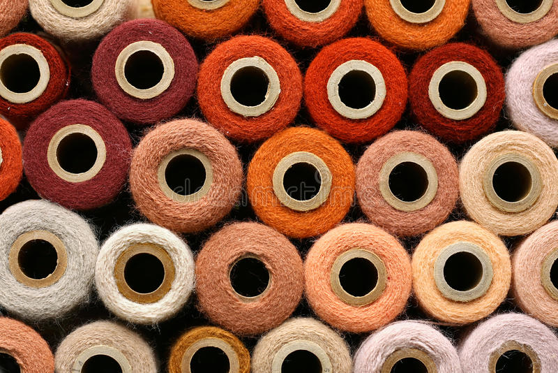 Colorful Collection of Vintage Spools of Craft Yarn. A large collection of Orange and other colorful vintage craft yarn spools gathered as a background royalty free stock images