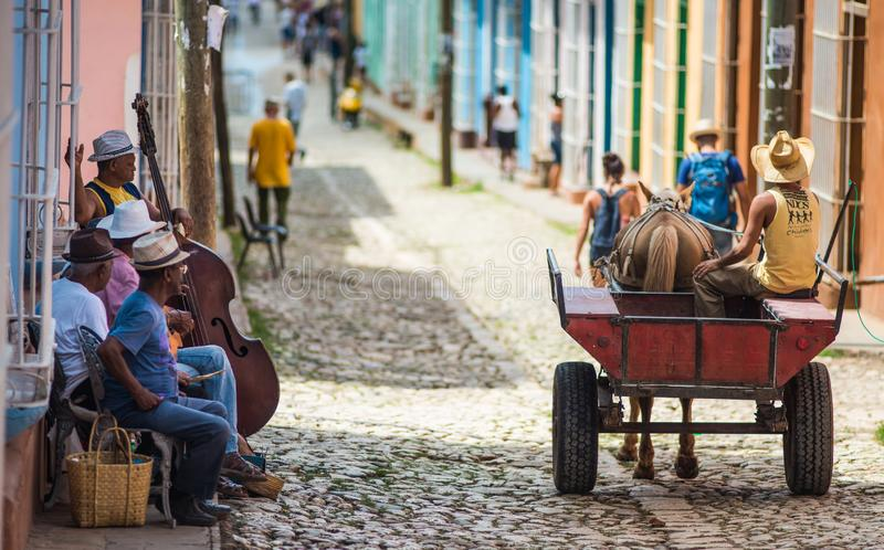 Colorful Colonial ancient town with classic carriage, farmer, cobblestone street in Trinidad, Cuba, America. royalty free stock photography