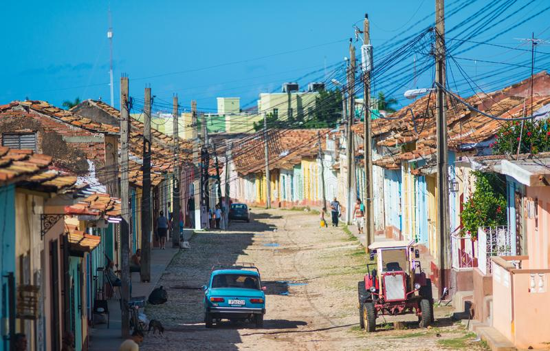 Colorful Colonial Caribbean historic village town with cobblestone street, classic car and house, Cuba, America. royalty free stock photos