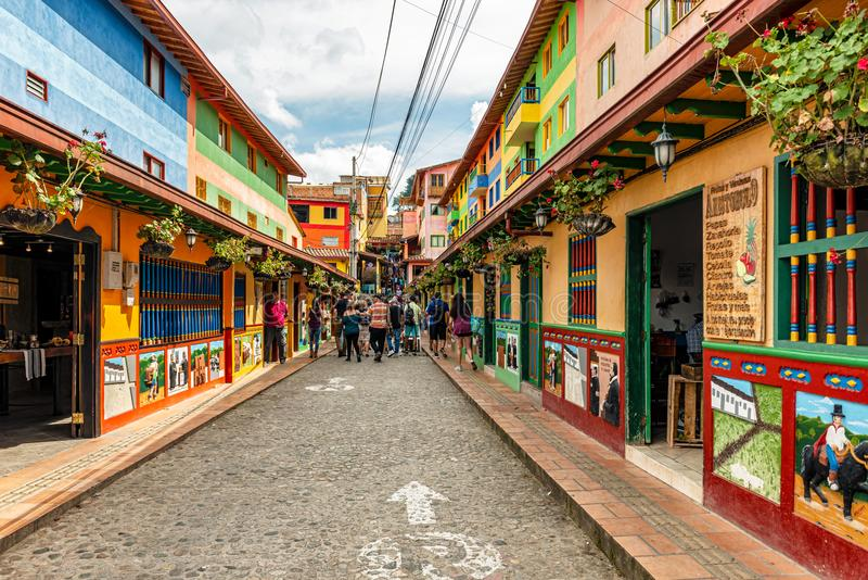 Colorful colonial houses on a cobblestone street in Guatape, Ant. Guatape, Colombia – March 27, 2018: Tourists walking by Colorful colonial houses on a stock photos
