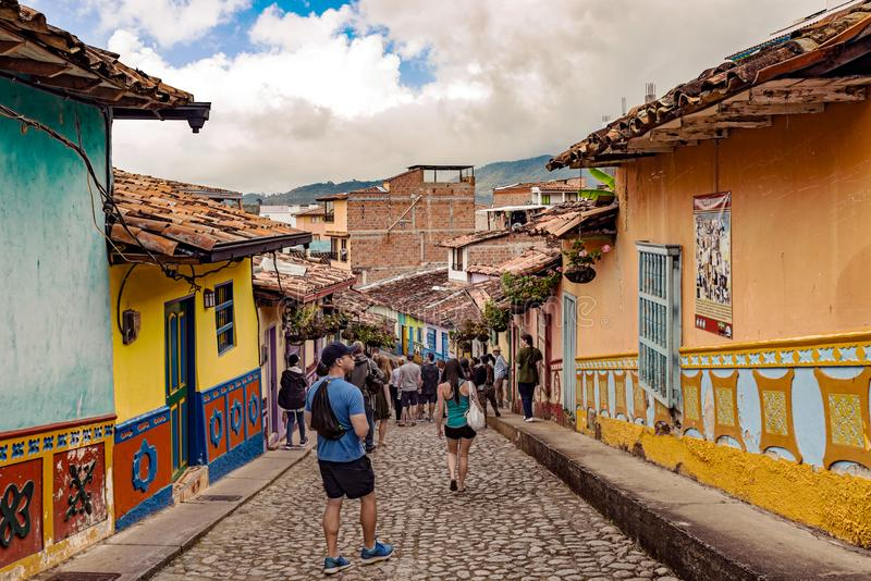Colorful colonial houses on a cobblestone street in Guatape, Ant. Guatape, Colombia – March 27, 2018: Tourists walking by Colorful colonial houses on a stock image