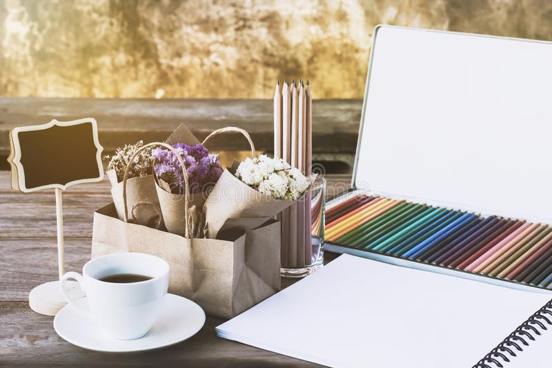 Colorful Color pencils for art drawing. Notebook of blank pages. With coffee cup and flower bouquet on wooden table background. Concept still life business or royalty free stock images