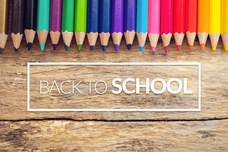 Colorful color pencils on old wooden background table with text back to school in white border frame royalty free stock photography