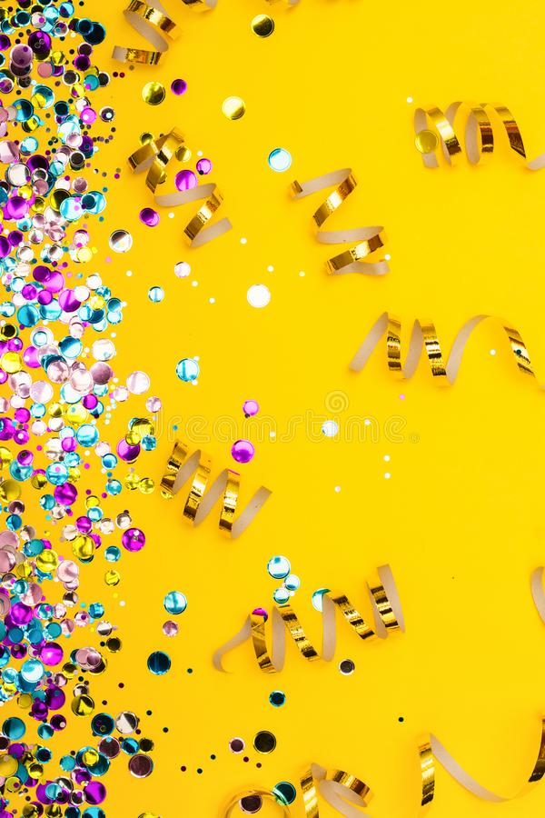 Colorful confetti and golden coiled streamers on yellow background royalty free stock images
