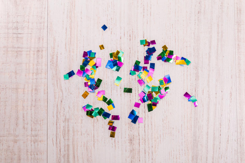 Colorful confetti on wood background. Scattered randomly stock image