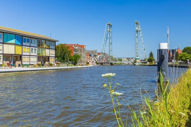 Colorful contemporary style houses and vertical lift bridge crossing the river Gouwe, Boskoop, the Netherlands. View over water at contemporary style houses and royalty free stock photo