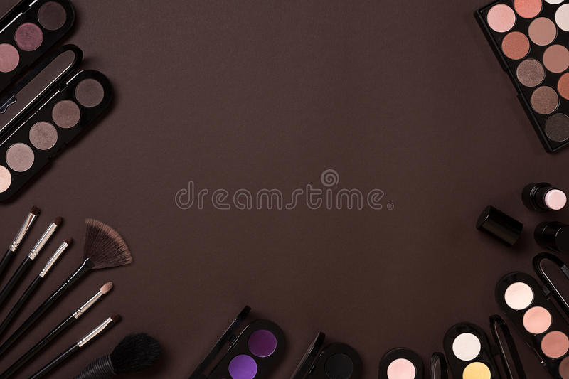 Colorful cosmetics on brown workplace with copy space. Cosmetics make up artist objects: lipstick, eye shadows, powder royalty free stock images