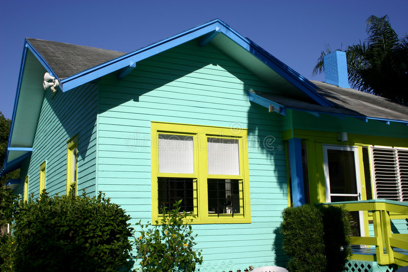 Colorful Cottage. Small green cottage with blue and yellow trim royalty free stock photo