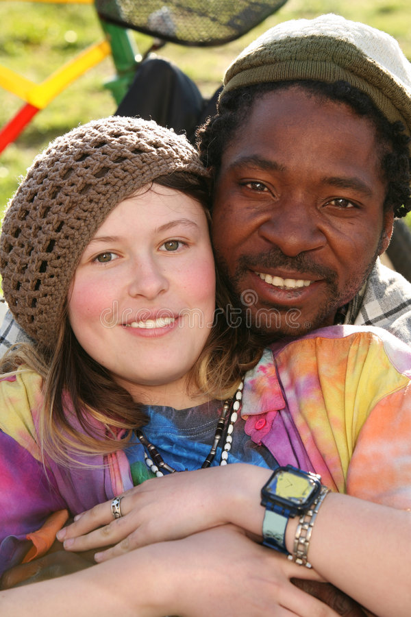 Colorful couple. A fun colorful multicultural couple (black man and white girl) enjoying spring sun on the grass in the park. Part of a bicycle visible in the stock photography