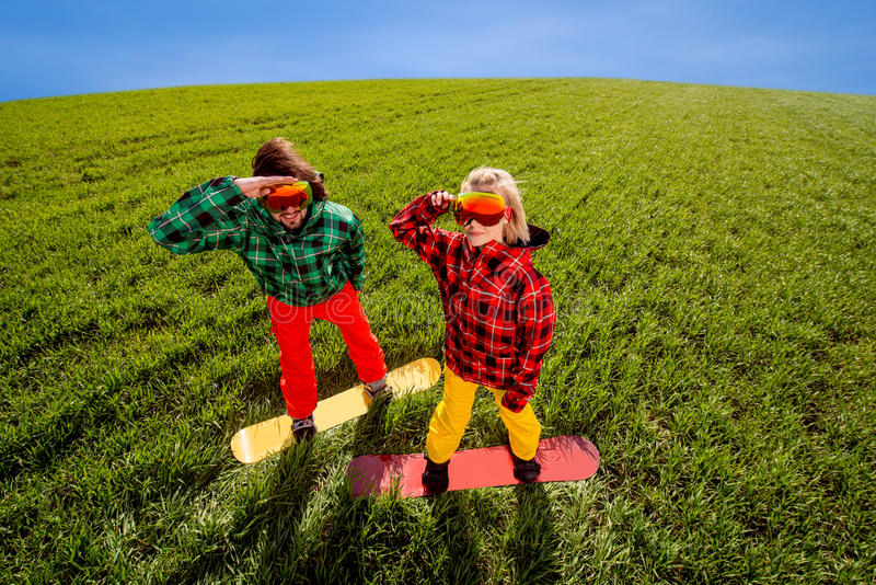 Colorful couple snowboarding on the grass in greenfield. Colorful couple snowboarding on the grass in the greenfield royalty free stock images