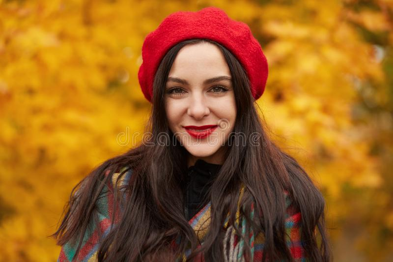 Colorful, cozy autumn, fashion concept. Outdoor portrait of young beautiful smiling girl wearing red beret. Model wrapped in royalty free stock images