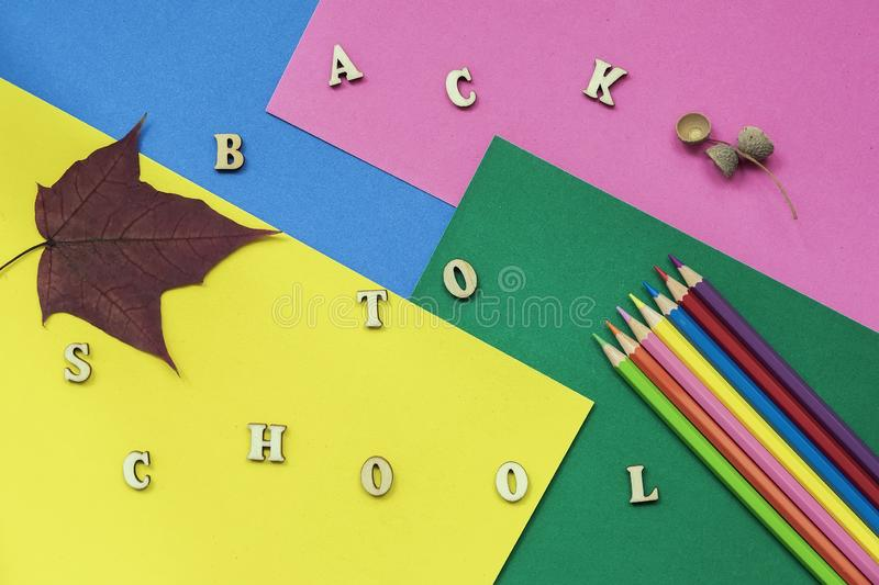 Colorful crayons, maple leaf and Back to school text, wooden letters on colored paper sheets. Concept of education royalty free stock image