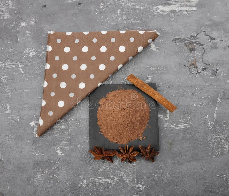 Cocoa powder, cinnamon stick and star anis on concrete. Colorful and crisp image of cocoa powder, cinnamon stick and star anis on concrete royalty free stock images