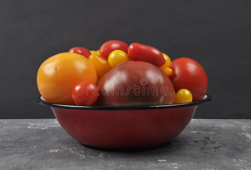 Variety of tomato cultivars in enamel bowl on concrete stock images