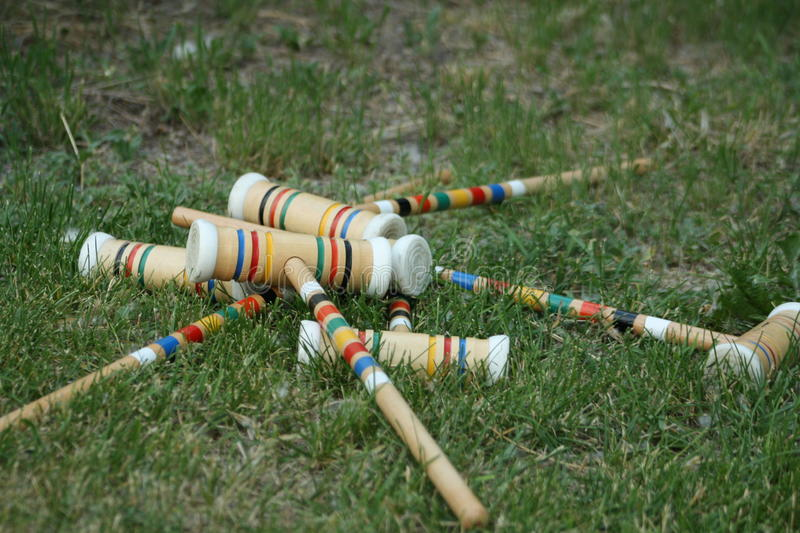 Colorful croquet mallets. In a jumbled pile after playing a summer game on the lawn royalty free stock photos