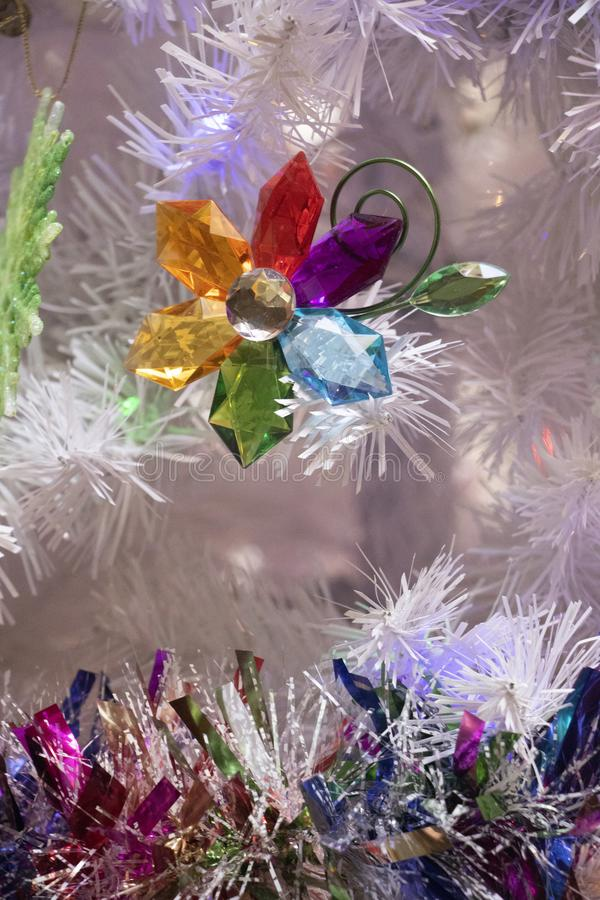 Colorful Crystal Flower on a White Christmas Tree royalty free stock photo