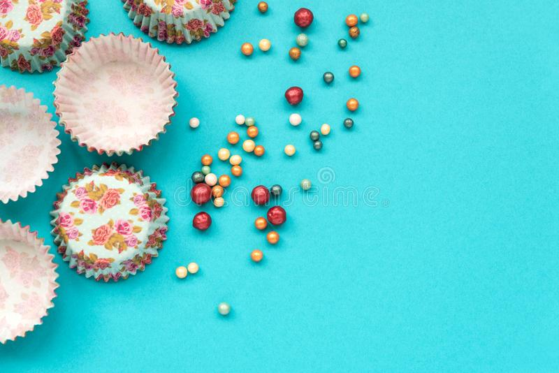 Colorful cupcake cases and sugar sprinkling on blue pastel background. Top view. Flat lay. Copy space. Baking utensils for cooking stock photography
