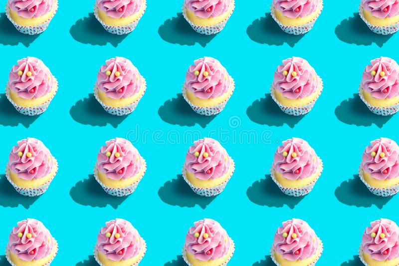 Colorful cupcake pattern on pastel blue background. Creative minimal party concept royalty free stock photo