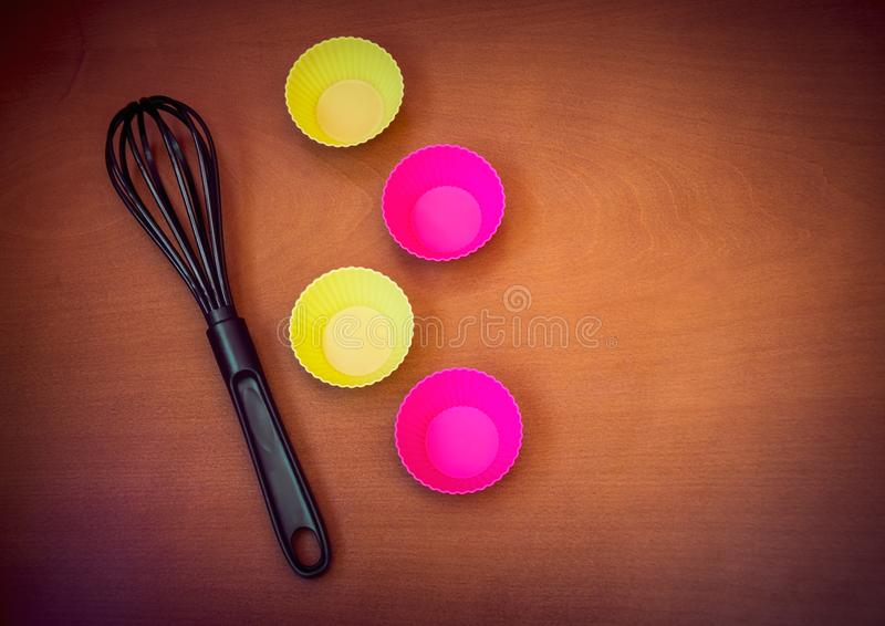 Colorful cupcake silicon baking cups and black whisk. Over wooden background royalty free stock photography
