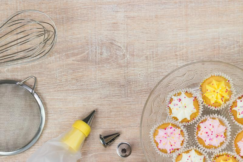 Colorful cupcakes and baking tools on a wooden table background. royalty free stock images