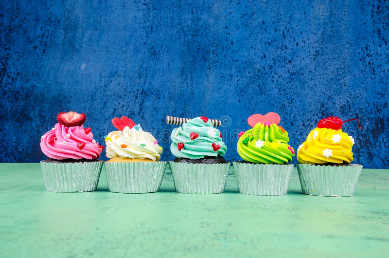 Colorful cupcakes. On a wooden background royalty free stock photos