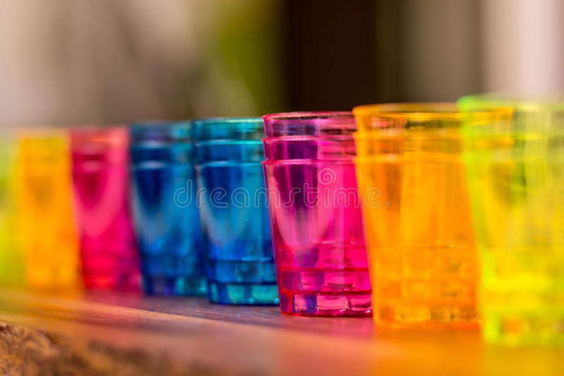 Colorful cups for cocktails lined up next to each other on a wooden surface stock image
