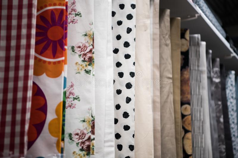 Colorful curtain samples hanging from hangers on rail in a display retail store Multiple color fabric texture samples stock photos