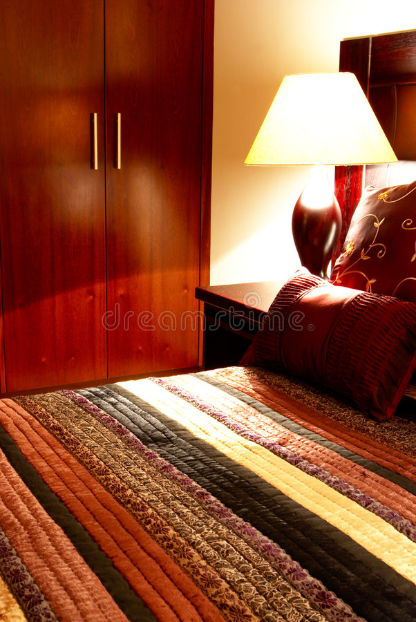 Colorful cushions on the bed. Colorful cushions on a bed in a guest lodge with the cupboard in the back stock photo