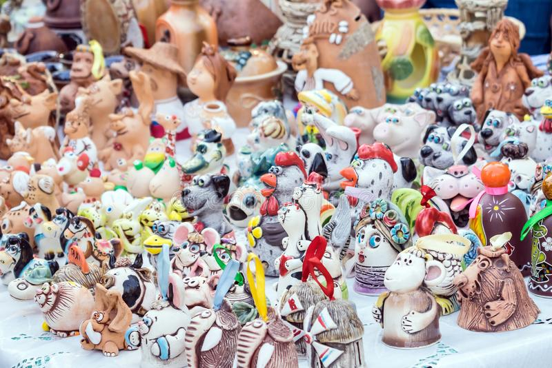 Colorful cute souvenir decorative clay bells, wind chimes, toys, dolls, figurines of animals and people. Handmade souvenir royalty free stock photo