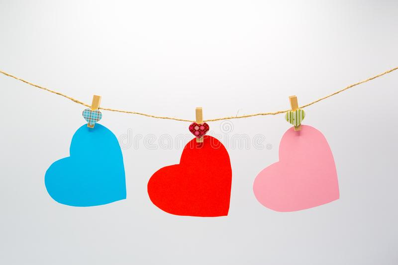 Colorful cutting paper hearts hanging rope with wooden clip for Happy Valentine`s Day. On white background stock images