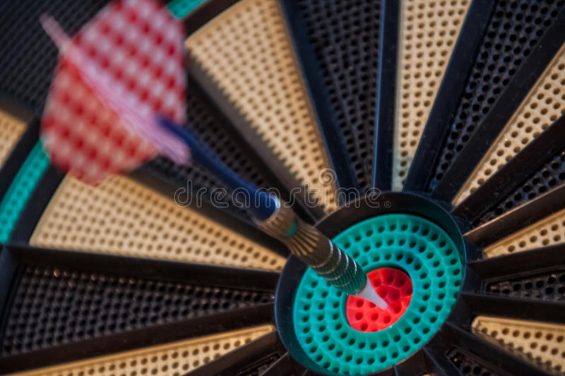 Colorful dart and target with green, yellow and red colors at th. E dartboard center stock images
