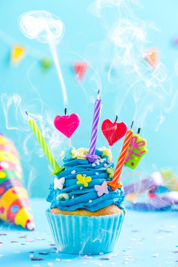 Colorful decorated cupcake with candles blow up royalty free stock photo