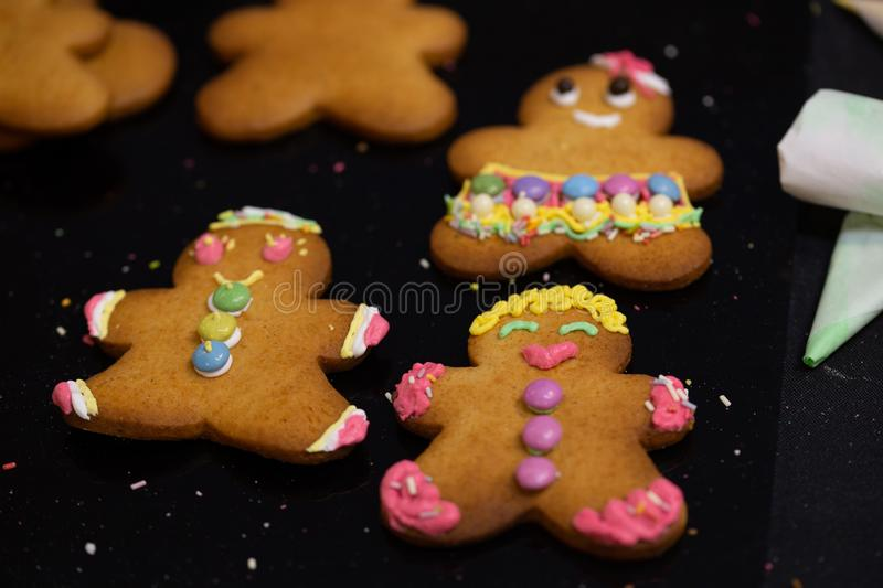 Colorful decorated ginger bread figurines, sweets and candy, made by children. Colorful decorated ginger bread figurines on tray, sweets and candy, made by royalty free stock photo